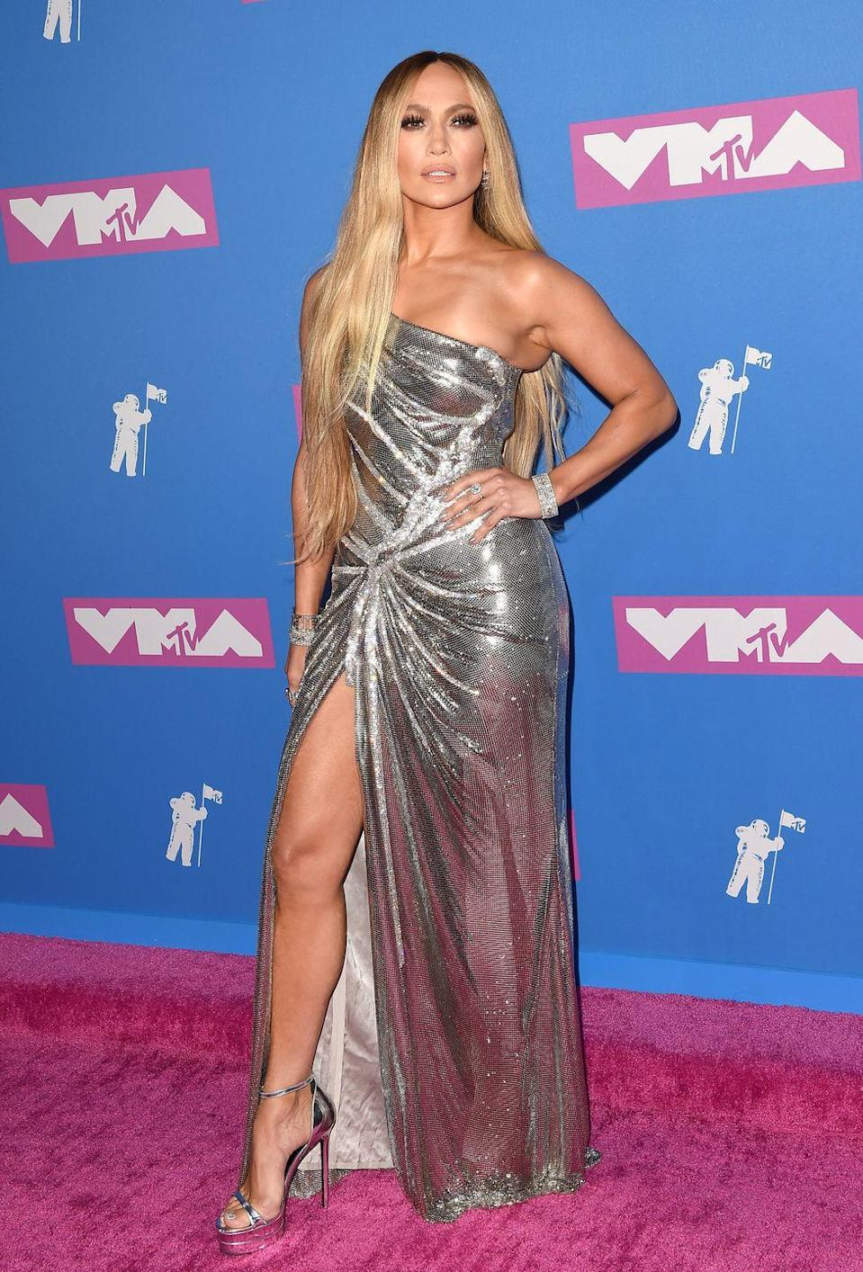 <p>Here, she arrives at the MTV Video Music Awards in New York City channeling a very chic disco ball in an asymmetrical sequin gown and silver high heels. </p>