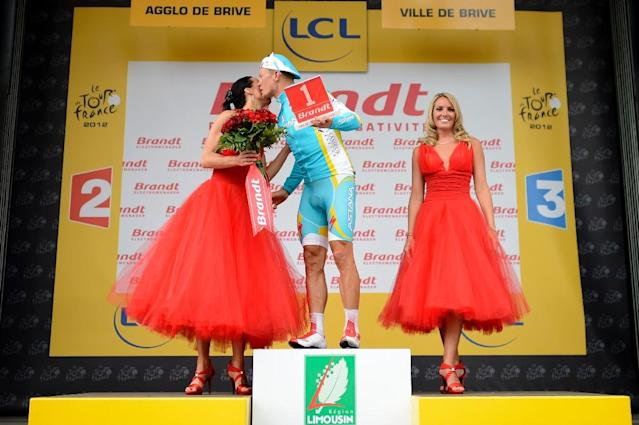 Kazakstan's Alexandre Vinokourov kisses a hostess as he celebrates on the podium his combativity prize at the end of the 222.5 km and eighteenth stage of the 2012 Tour de France cycling race in Brive-la-Gaillarde, France, on July 20, 2012 (AFP Photo/JEFF PACHOUD)