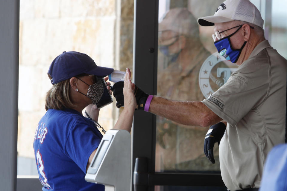 Amid concerns of the spread of the virus that causes COVID-19, a baseball fan has their temperature checked by a security guard before being allowed to tour Globe Life Field, home of the Texas Rangers baseball team in Arlington, Texas, Monday, June 1, 2020. The coronavirus pandemic has forced sports teams and their leagues to evaluate how they will welcome back fans. (AP Photo/LM Otero)