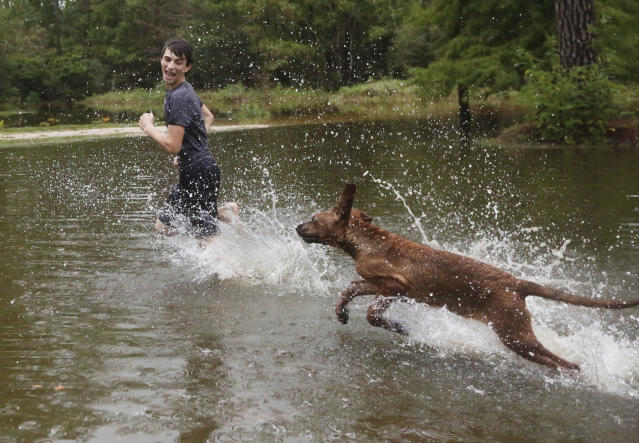 "<p>Tim Neilsen III, 16, is chased by his dog ""Chevy"" through flood waters that filled their front yard after Hurricane Nate, Sunday, Oct. 8, 2017, in Coden, Ala. (Photo: Brynn Anderson/AP) </p>"