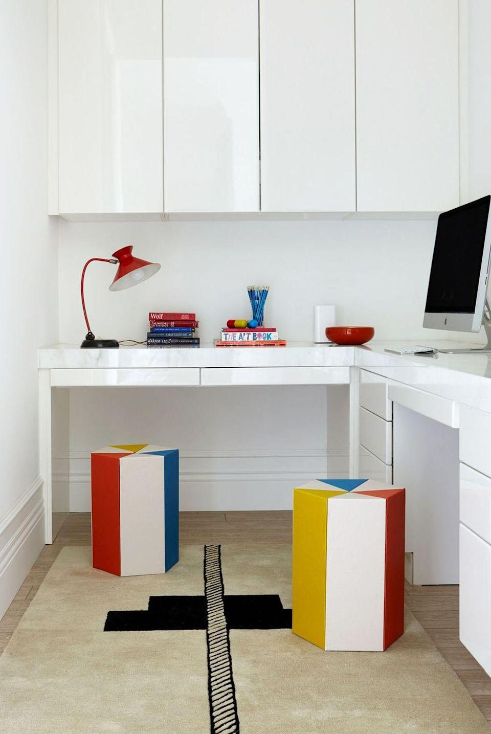 """<p>Opt for glossy white lacquered cabinets and furniture for a small makeshift home office in the corner of a larger room or if you're converting a walk-in closet and need to maximize light. The high sheen gives a mirror effect, reflecting light to make it feel like a larger, more open space. Designer <a href=""""http://www.rajirm.com/"""" rel=""""nofollow noopener"""" target=""""_blank"""" data-ylk=""""slk:Raji Radhakrishnan"""" class=""""link rapid-noclick-resp"""">Raji Radhakrishnan</a> gave <a href=""""https://www.housebeautiful.com/design-inspiration/house-tours/a30696950/raji-rm-piet-boon-virginia/"""" rel=""""nofollow noopener"""" target=""""_blank"""" data-ylk=""""slk:this"""" class=""""link rapid-noclick-resp"""">this</a> home office some pops of fun and vibrancy with primary-colored stools and a graphic rug.</p>"""