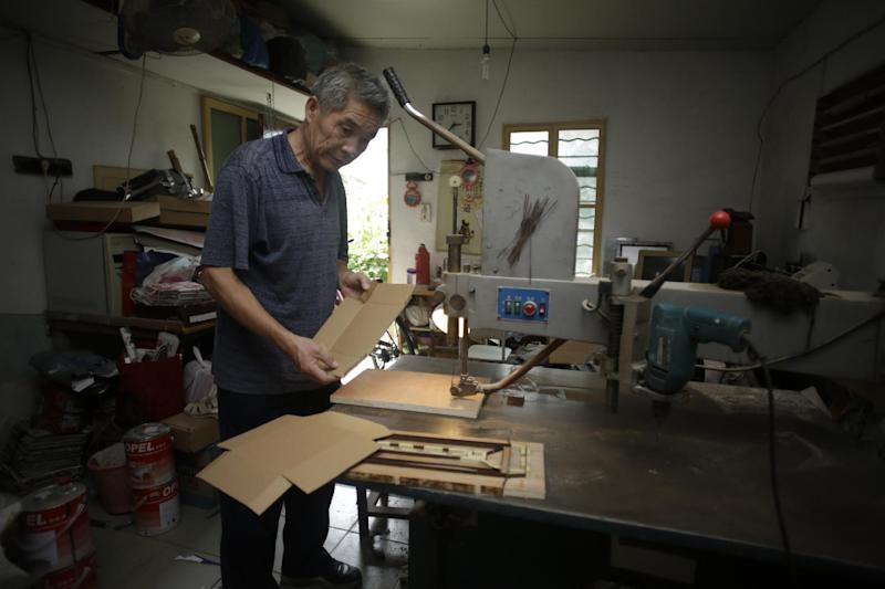 """In this Sept. 9, 2013 photo, Dong Linhua, 59, works at his workshop in Shanghai. """"I heard that the authorities might postpone the age of the retirement, but I sure hope not, since I've already worked for almost 42 years,"""" says Dong. (AP Photo/Eugene Hoshiko)"""