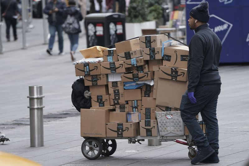 FILE PHOTO: An Amazon delivery person walks in Times Square following the outbreak of Coronavirus disease (COVID-19), in the Manhattan borough of New York City