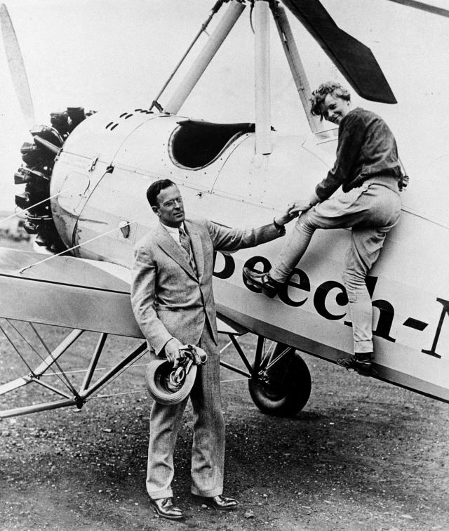 American aircraft pilot Amelia Earhart is assisted by her husband, George Palmer Putnam, as she climbs out of the cockpit of her autogiro after completing a transcontinental flight to the West Coast and back, at the Metropolitan Airport in Newark, N.J., on June 22, 1931. (AP Photo)