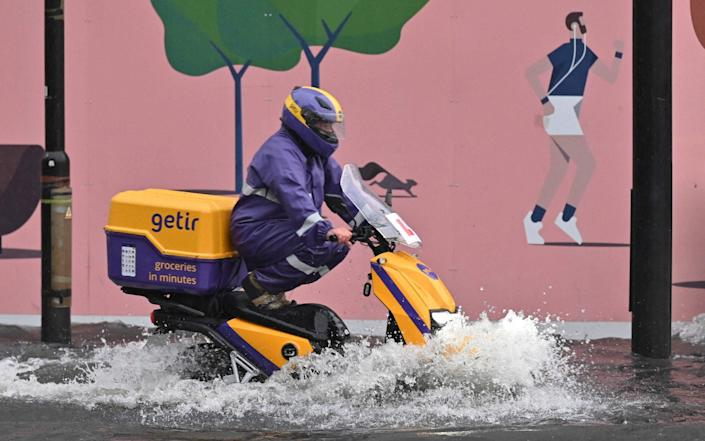 A motorcyclist drives through deep water on a flooded road in London - AFP