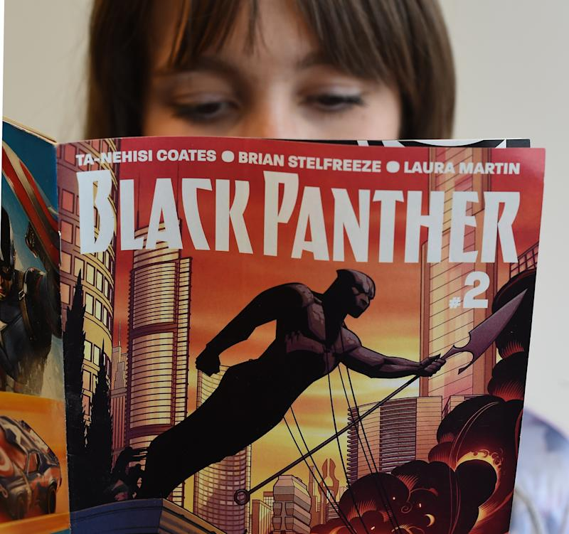 "In this photo illustration a woman reads a copy of the Black Panther (T'Challa) a fictional superhero appearing in comic book published by Marvel Comics in New York May 17, 2016. Captain America and Iron Man may be the stars of Marvel's latest comic-book blockbuster, but Black Panther -- making his big-screen debut -- is most definitely the superhero of the moment. Black Panther, the warrior king of the futuristic fictional African country Wakanda, is starring in a new comic book series that is doing booming sales, and will be the first black hero to get a standalone film, in 2018. The new comic series -- written by acclaimed author Ta-Nehisi Coates, a leading voice on race issues in America -- debuted in April, and so far 330,000 copies of the first issue alone have been sold, according to Marvel. / AFP / TIMOTHY A. CLARY / TO GO WITH AFP STORY BY THOMAS URBAIN-""Black Panther, Marvel's African hero, in the spotlight"" (Photo credit should read TIMOTHY A. CLARY/AFP via Getty Images)"