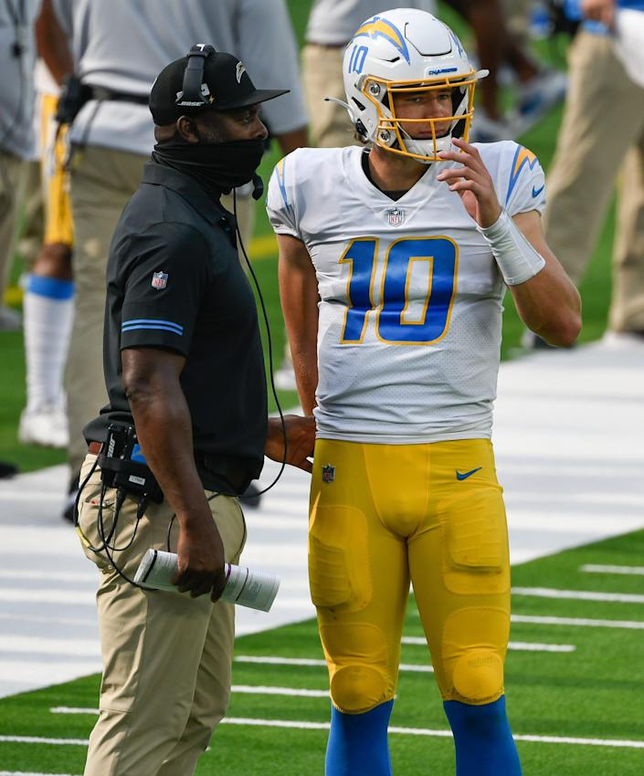 Los Angeles Chargers head coach Anthony Lynn goes over a play with quarterback Justin Herbert on Sept. 27, 2020 in Inglewood, Calif.