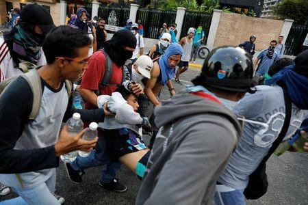 A injured demonstrator is helped by others during a rally against Venezuela's President Nicolas Maduro's government in Caracas
