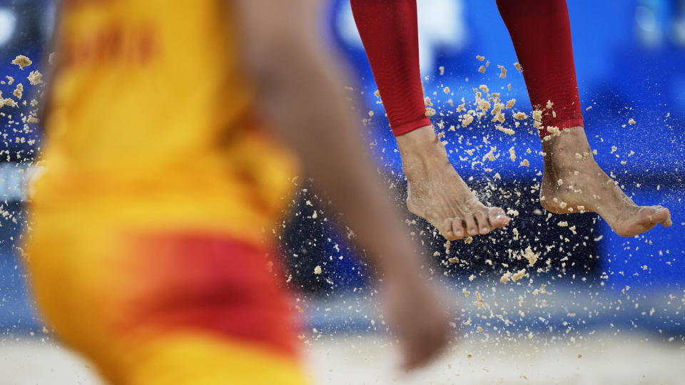 Feet and sand fly during the beach volleyball match between Norway and Spain at the 2020 Summer Olympics, Monday, July 26, 2021, in Tokyo, Japan. (AP Photo/Petros Giannakouris)