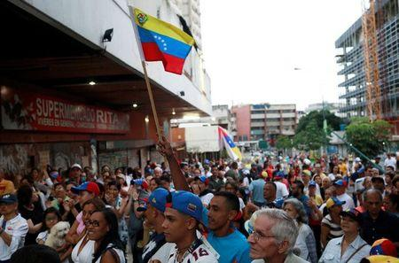 Opposition supporters wait near a polling station for results of an unofficial plebiscite against President Nicolas Maduro's government and his plan to rewrite the constitution, in Caracas