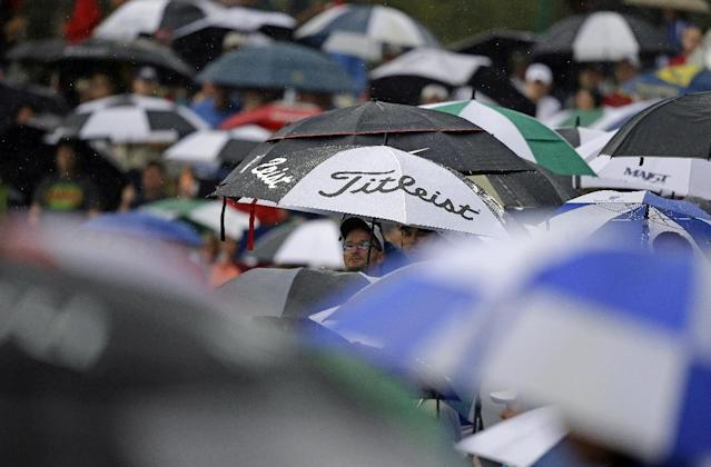 A fan watches from under an umbrella along the fifth hole during the four-ball matches at the Presidents Cup golf tournament at Muirfield Village Golf Club Saturday, Oct. 5, 2013, in Dublin, Ohio. (AP Photo/Darron Cummings)