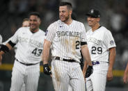 Colorado Rockies' C.J. Cron, front, smiles after driving in the winning run against the Milwaukee Brewers in the 10th inning of a baseball game Friday, June 18, 2021, in Denver. The Rockies won 6-5. (AP Photo/David Zalubowski)
