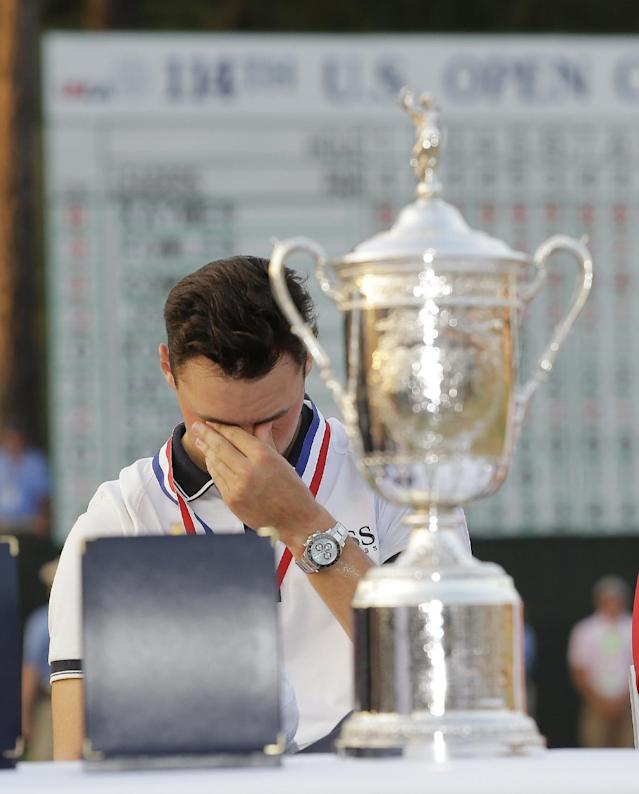 Martin Kaymer, of Germany, wipes his eyes behind the trophy after wining the U.S. Open golf tournament in Pinehurst, N.C., Sunday, June 15, 2014. (AP Photo/Eric Gay)