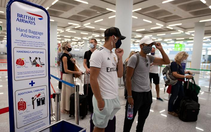 British tourists wait to check in for a flight to London at the airport in Palma de Mallorca - JAIME REINA / AFP