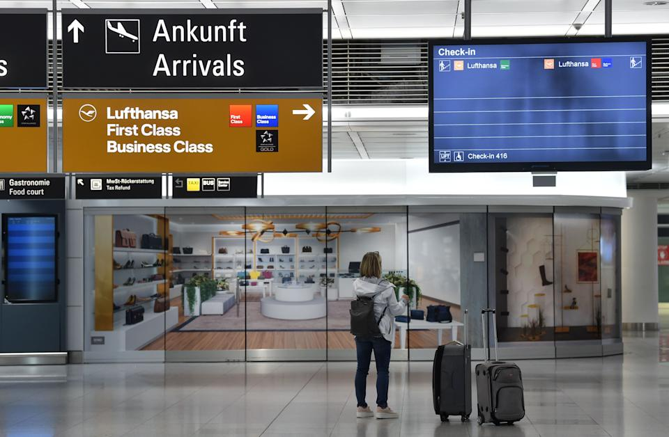 """A passenger stand in front of a check-in screen at the """"Franz-Josef-Strauss"""" airport in Munich. Germany has warned it will have to close its borders to prevent the new variant (AFP via Getty Images)"""