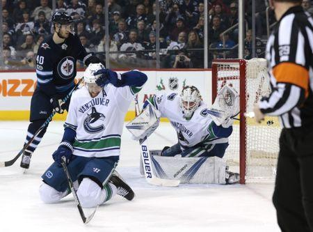Dec 11, 2017; Winnipeg, Manitoba, CAN; Winnipeg Jets left wing Nikolaj Ehlers (27) (not in photo) scores on Vancouver Canucks goalie Jacob Markstrom (25) in second period action as Vancouver Canucks defenseman Alexander Edler (23) tries to block the shot at Bell MTS Place. Mandatory Credit: James Carey Lauder-USA TODAY Sports