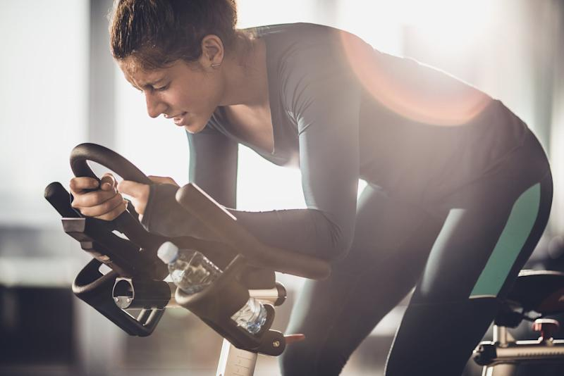 Determined female athlete making an effort on a spinning class in a health club.