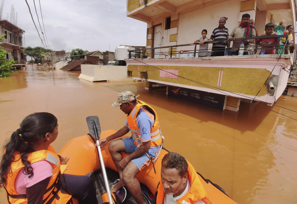People stranded in flood waters watch others being rescued at Kolhapur in western Maharashtra state, India, Saturday, July 24, 2021. Officials say landslides and flooding triggered by heavy monsoon rain have killed more than 100 people in western India. More than 1,000 people trapped by floodwaters have been rescued. (AP Photo)
