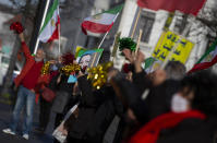 People wave flags and confetti after the trial of four persons, including an Iranian diplomate and Belgian-Iranian couple at the courthouse in Antwerp, Belgium, Thursday, Feb. 4, 2021. An Iranian official on Thursday was convicted of masterminding a thwarted bomb attack against an exiled Iranian opposition group in France in 2018 and sentenced to 20 years in prison by a Belgian court that rejected his claim of diplomatic immunity. Assadollah Assadi, a Vienna-based diplomat detained in Belgium, refused to testify during his trial last year, invoking his diplomatic status. He did not attend Thursday's hearing at the Antwerp courthouse. (AP Photo/Virginia Mayo)
