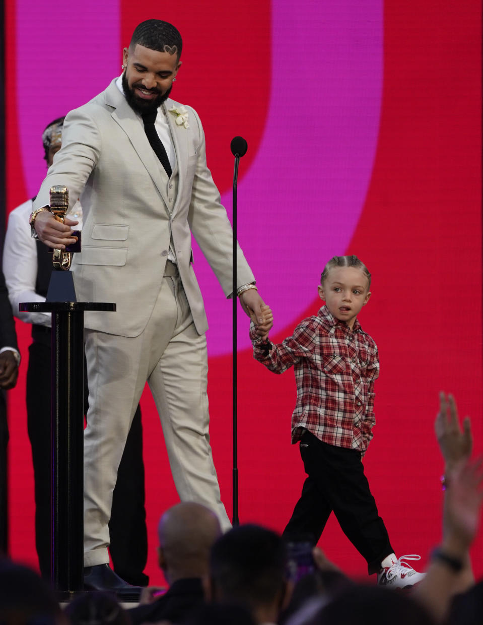 Drake accepts the artist of the decade award as he holds his son Adonis Graham at the Billboard Music Awards on Sunday, May 23, 2021, at the Microsoft Theater in Los Angeles. (AP Photo/Chris Pizzello)