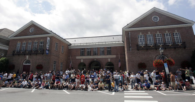 FILE - This June 16, 2008 file photo shows baseball fans in front of the National Baseball Hall of Fame and Museum in Cooperstown, N.Y. There are many destinations of interest to baseball fans around the country outside ballparks from museums and statues to historic homes. (AP Photo/Mike Groll, File)