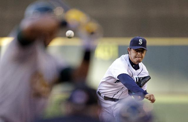 Seattle Mariners starting pitcher Hisashi Iwakuma throws against the Oakland Athletics in the first inning of a baseball game Saturday, July 12, 2014, in Seattle. (AP Photo/Elaine Thompson)