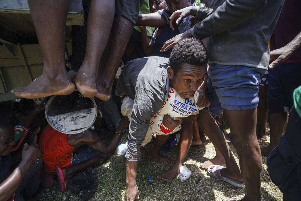 A resident crawls away with a donated bag of rice after residents temporarily overtook a truck loaded with relief supplies, in Vye Terre, Haiti, Friday, Aug. 20, 2021. Private aid and shipments from the U.S. government and others were arriving in the country's southwestern peninsula that was struck by a 7.2 magnitude quake on Aug. 14. (AP Photo/Fernando Llano)