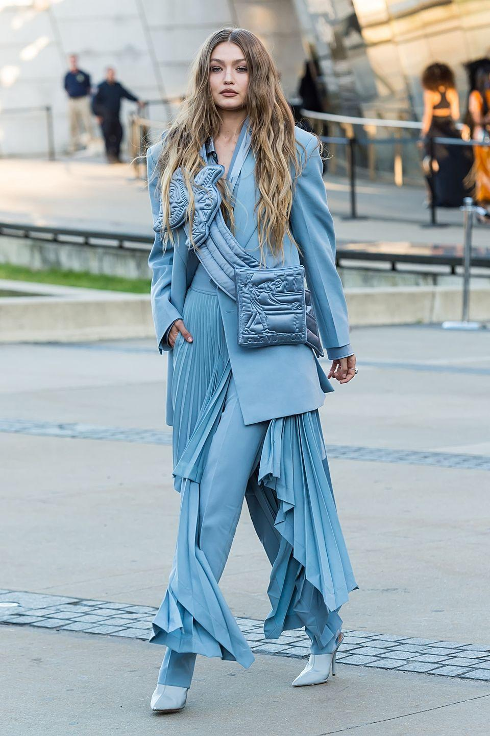 <p>In an icy blue pantsuit and pleated skirt with white pumps.</p>