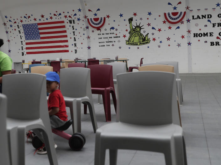 FILE - In this Friday, Aug. 23, 2019, file photo, immigrants seeking asylum watch a movie in a recreational area at the ICE South Texas Family Residential Center in Dilley, Texas. The state of California is freeing up to $28 million to help asylum-seekers released in the U.S. with notices to appear in court with hotels, medical screenings, and transportation. California's generosity is a stark contrast to Arizona and Texas, where border state officials have challenged and sharply criticized President Joe Biden's immigration policies. (AP Photo/Eric Gay, File)