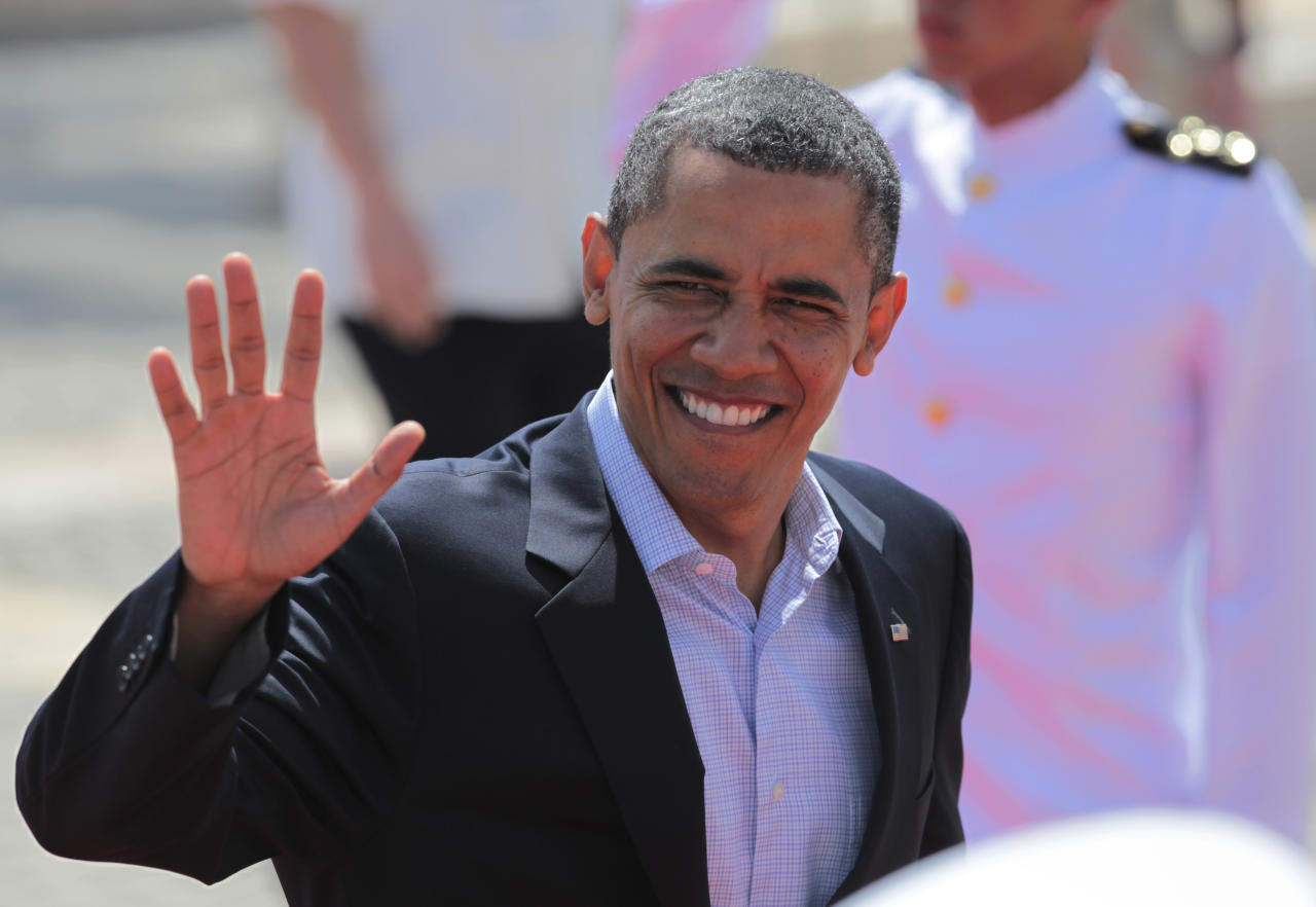 President Barack Obama waves as he arrives at the Convention Center for the second working session of the sixth Summit of the Americas in Cartagena, Colombia, Sunday April 15, 2012. (AP Photo/Fernando Llano)