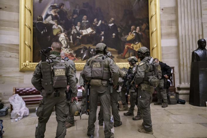 After violent protesters loyal to President Donald Trump stormed the U.S. Capitol today, a tactical team with ATF gathers in the Rotunda to provide security for the continuation of the joint session of the House and Senate to count the Electoral College votes cast in November's election, at the Capitol in Washington, Wednesday, Jan. 6, 2021. (AP Photo/J. Scott Applewhite)