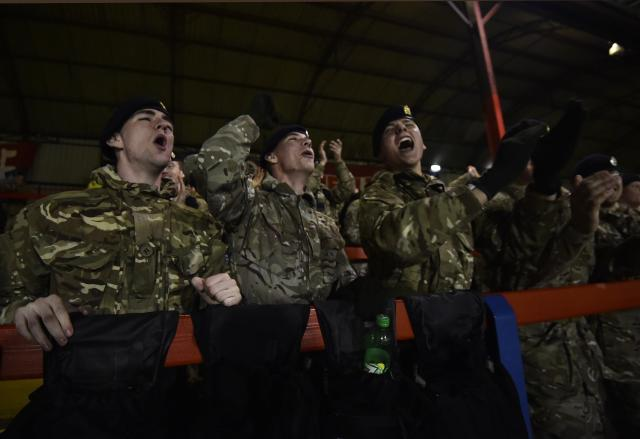 British army personnel celebrate a goal as they watch a soccer match between the British Army and German Bundeswehr at Aldershot Town FC stadium in Aldershot in south England, December 17, 2014. The two teams were playing each other in a 'Game of Truce' soccer match, commemorating 100 years since the famous peaceful interlude to fighting in World War I when members of the opposing British and German forces played a game of soccer in No Man's Land on Christmas Day 1914. REUTERS/Toby Melville (BRITAIN - Tags: SPORT SOCCER POLITICS ANNIVERSARY CONFLICT MILITARY)