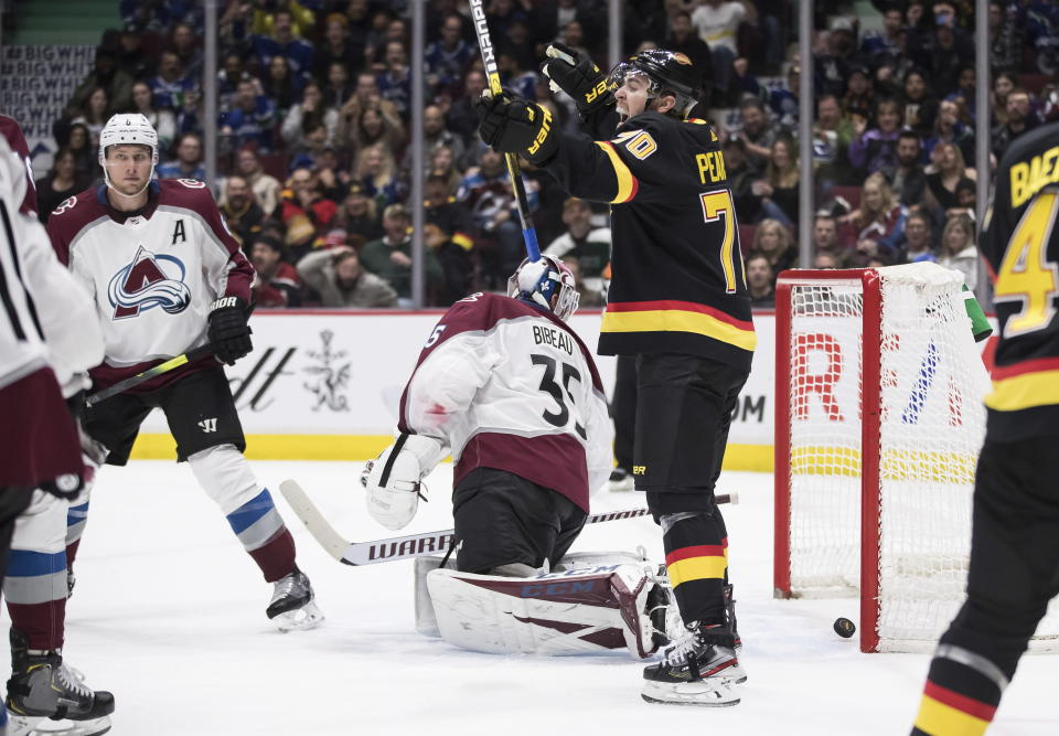 Vancouver Canucks' Tanner Pearson (70) celebrates Adam Gaudette's goal against Colorado Avalanche goalie Antoine Bibeau (35) during the second period of an NHL hockey game Saturday, Nov. 16, 2019, in Vancouver, British Columbia. (Darryl Dyck/The Canadian Press via AP)