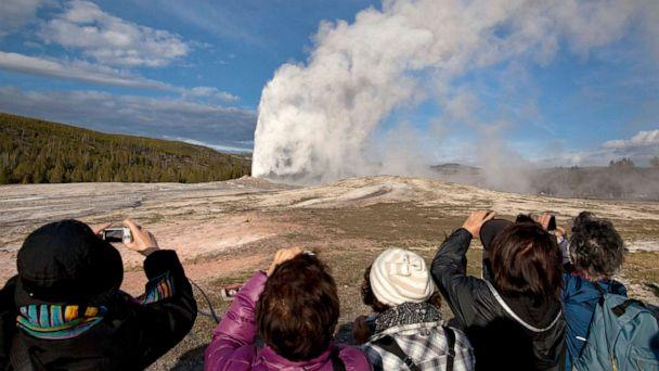 PHOTO: In this file photo taken on May 21, 2011, tourists photograph Old Faithful erupting on schedule late in the afternoon in Yellowstone National Park, Wyoming. (AP Photo/Julie Jacobson, File)