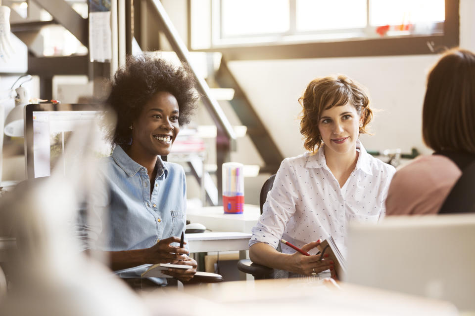 Happy businesswomen discussing with female colleague in office