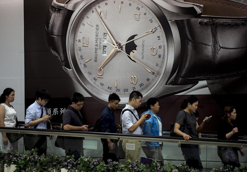 People are seen on a moving walkway next to a large advertisement for a luxury watch, in Hong Kong, on August 7, 2014 (AFP Photo/Alex Ogle)