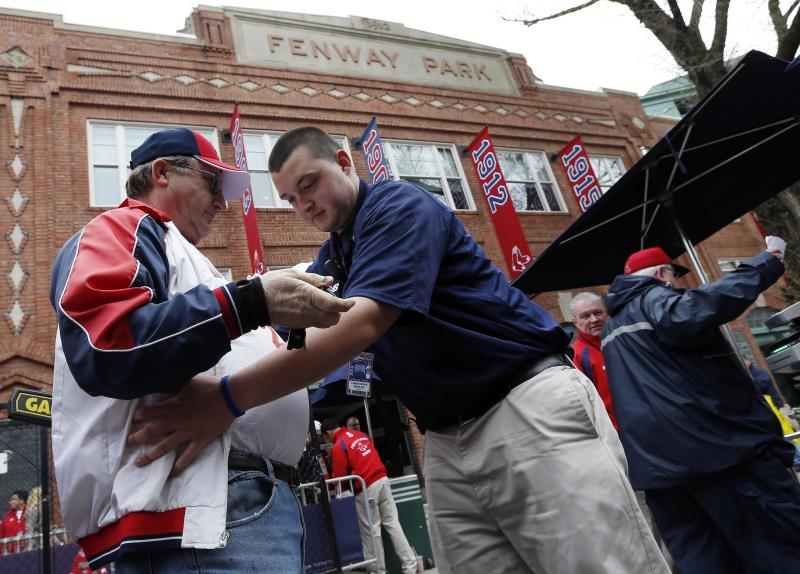Fans pass through security before entering Fenway Park for a baseball game between the Boston Red Sox and the Kansas City Royals in Boston, Saturday, April 20, 2013. (AP Photo/Michael Dwyer)