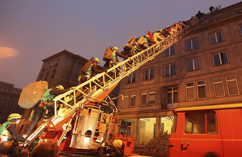 Climate activists walk up the ladder to the roof of the Economy Ministry in Warsaw, Poland Monday, Nov. 18, 2013. They are there to protest a coal conference opening to coincide with U.N. talks on preventing global warming, that is also the result of greenhouse gases coming from burning coal. (AP Photo/Czarek Sokolowski)