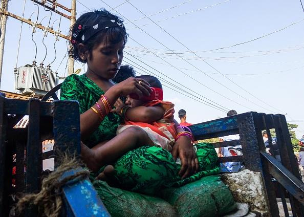 A girl holds a baby at the Aung Mingalar quarter for Rohingya Muslims.