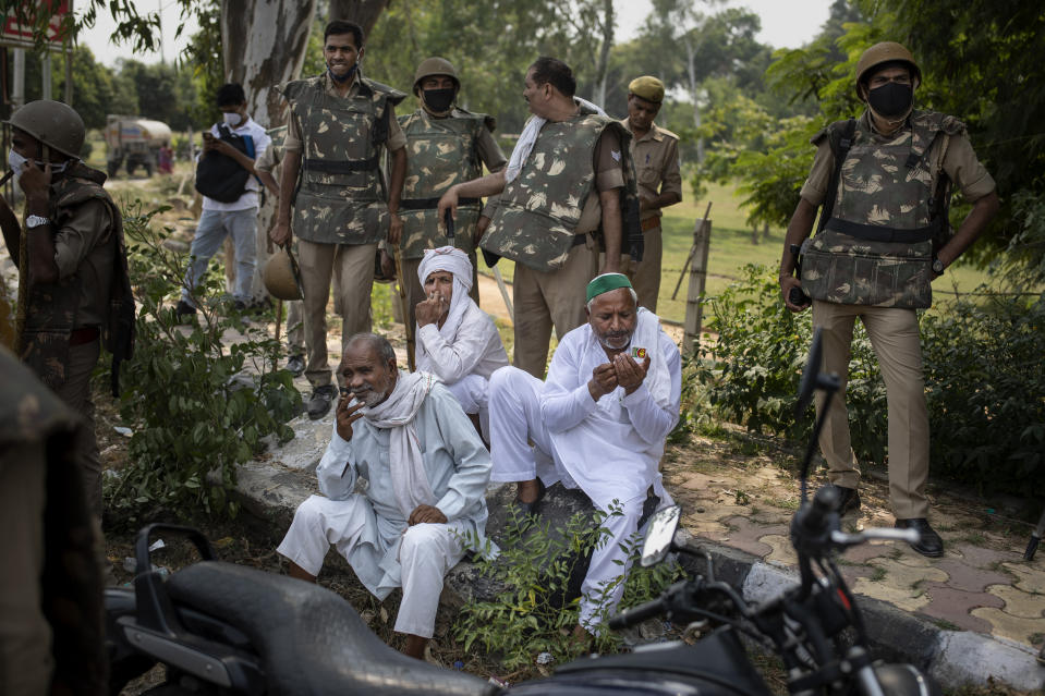 Indian policemen stand guard as elderly Indian farmers sit in the shade during a protest in Noida on the outskirts of New Delhi, India, Friday, Sept. 25, 2020. Hundreds of Indian farmers took to the streets on Friday protesting new laws that the government says will boost growth in the farming sector through private investments, but they fear these are likely to be exploited by private players for buying their crops cheaply. (AP Photo/Altaf Qadri)