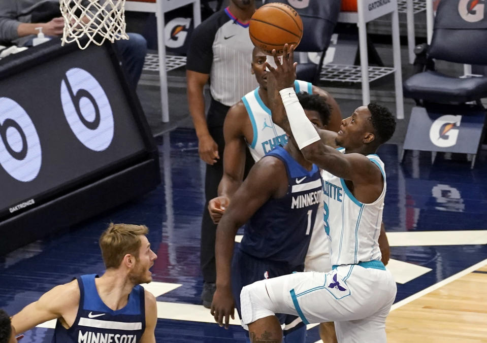 Charlotte Hornets' Terry Rozier, right, lays the ball up in front of Minnesota Timberwolves' Anthony Edwards (1) and Jake Layman, left, during the first half of an NBA basketball game Wednesday, March 3, 2021, in Minneapolis. (AP Photo/Jim Mone)
