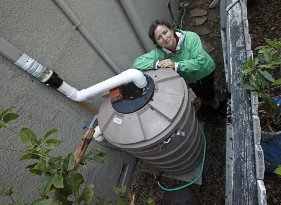 FILE - In this Feb. 28, 2014, file photo, Santa Monica, Calif., resident Josephine Miller stands next to her 200-gallon water storage tank that collects rain from her home's roof to water her garden. A major Southern California water agency has declared a water supply alert for the first time in seven years, Tuesday, Aug. 17, 2021 and is asking residents to voluntarily conserve. (AP Photo/Reed Saxon, File)