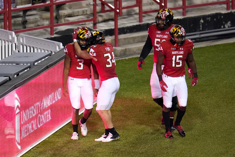 Maryland quarterback Taulia Tagovailoa (3) is congratulated by running back Jake Funk (34) after scoring a touchdown run against Minnesota during overtime of an NCAA college football game, Friday, Oct. 30, 2020, in College Park, Md. Maryland won 45-44 in overtime. (AP Photo/Julio Cortez)