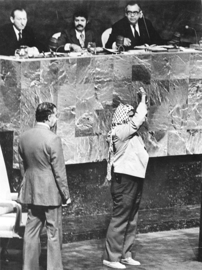 FILE - In this Wednesday, November 13, 1974 file photo, what appears to be a pistol holster protrudes from P.L.O. leader Yasser Arafat's jacket as he clasps his hands over his head during his appearance before the United Nations General Assemblyat U.N. Headquarters. One of Arafat's bodyguards reportedly told a newsman it was a gun. Sitting at the desk above Arafat are, from left, Secretary-General Kurt Waldheim, Abdel Aziz Bouteflika, president of the General Assembly and Bradford Morse, Undersecretary-General. Man behind Arafat is unidentified. Israeli Prime Minister Benjamin Netanyahu's use of a cartoon-like drawing of a bomb to convey a message over Iran's disputed nuclear program this week, follows in a long and storied tradition of leaders and diplomats using props to make their points at the United Nations. (AP Photo/File)