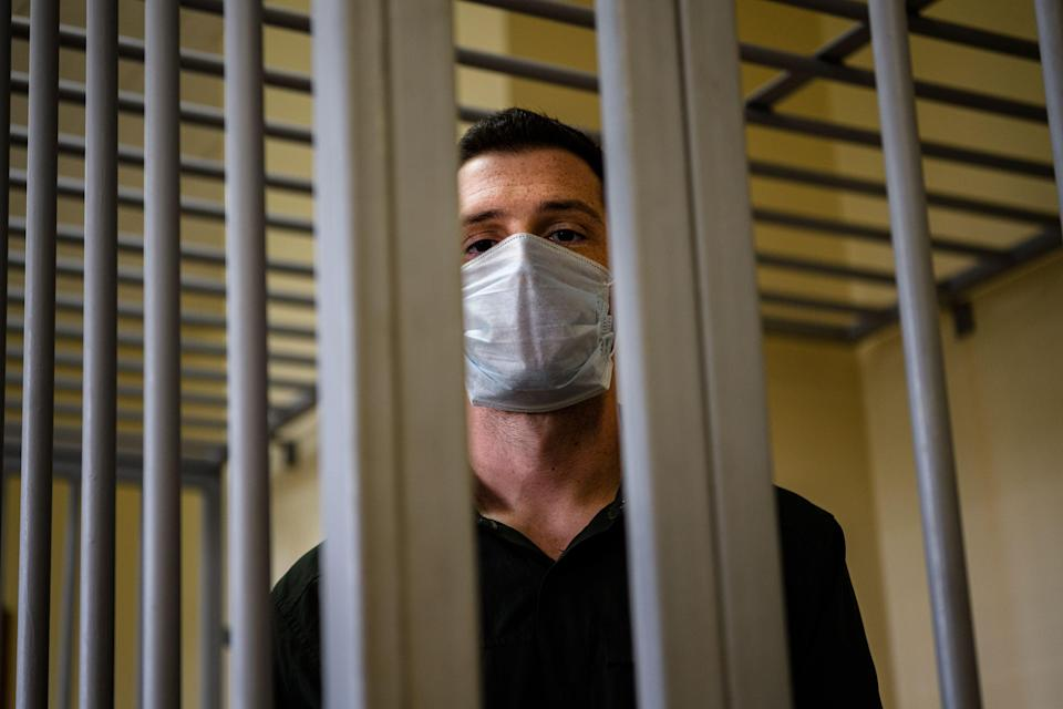 US ex-marine Trevor Reed, then charged with attacking police, stands inside a defendants' cage during his verdict hearing at Moscow's Golovinsky district court on 30 July, 2020.  (AFP via Getty Images)