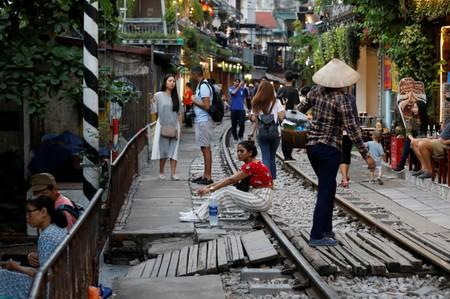 A woman sits on a railway track as tourists gather along it on a street in the Old Quarter of Hanoi, Vietnam