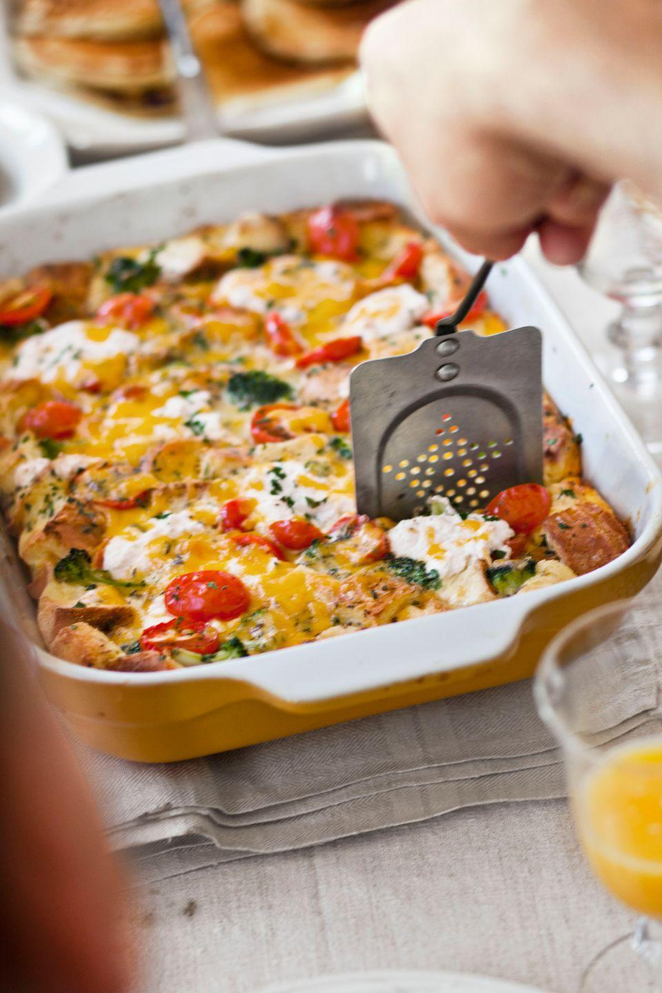 """<p>Comfort food doesn't get much better than a crowd-pleasing strata. You can assemble this <a href=""""https://www.countryliving.com/food-drinks/g13/cookbook-eggs-0407/"""" rel=""""nofollow noopener"""" target=""""_blank"""" data-ylk=""""slk:egg"""" class=""""link rapid-noclick-resp"""">egg</a> casserole—loaded with French bread, tomatoes, and broccoli, and topped with both Cheddar and ricotta cheeses—the night before.</p><p><strong><a href=""""https://www.countryliving.com/food-drinks/recipes/a4115/tomato-cheddar-strata-broccoli-recipe-clv0212/"""" rel=""""nofollow noopener"""" target=""""_blank"""" data-ylk=""""slk:Get the recipe"""" class=""""link rapid-noclick-resp"""">Get the recipe</a>.</strong></p>"""