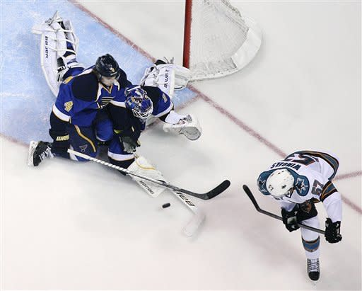 St. Louis Blues defenseman Kris Russell (4) and goaltender Brian Elliott defend against a shot by San Jose Sharks center Tommy Wingels during the third period in Game 2 of an NHL Stanley Cup first-round hockey playoff series Saturday, April 14, 2012, in St. Louis. The Blues won 3-0. (AP Photo/St. Louis Post-Dispatch, Chris Lee) EDWARDSVILLE INTELLIGENCER OUT; THE ALTON TELEGRAPH OUT