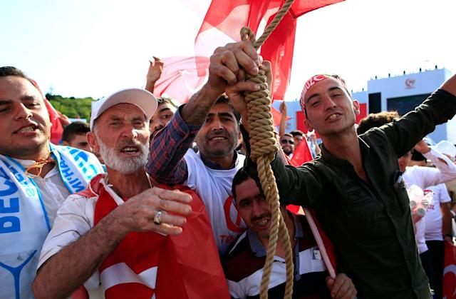 """<p>People pose with a hangman's knot as they take part in the """"National Unity March"""" to commemorate the one year anniversary of the July 15, 2016 botched coup attempt, in Istanbul, Saturday, July 15, 2017. (Photo: Lefteris Pitarakis/AP) </p>"""