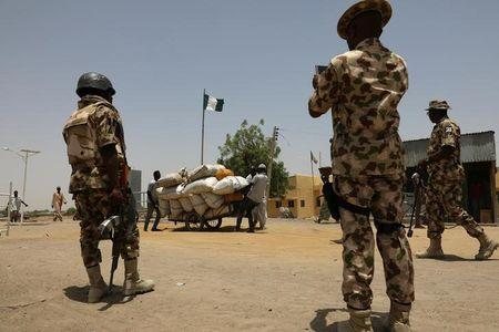 Men push a cart loaded with goods past soldiers at the boarder in Gamboru Ngala, Borno, Nigeria